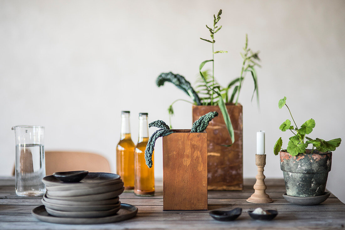 Stacked plates, drinks, houseplants and candle on rustic wooden table