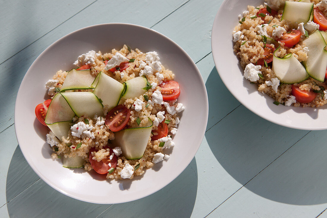Quinoa salad with feta, cherry tomatoes, courgette ribbons. garlic chives snipped and chilli pepper