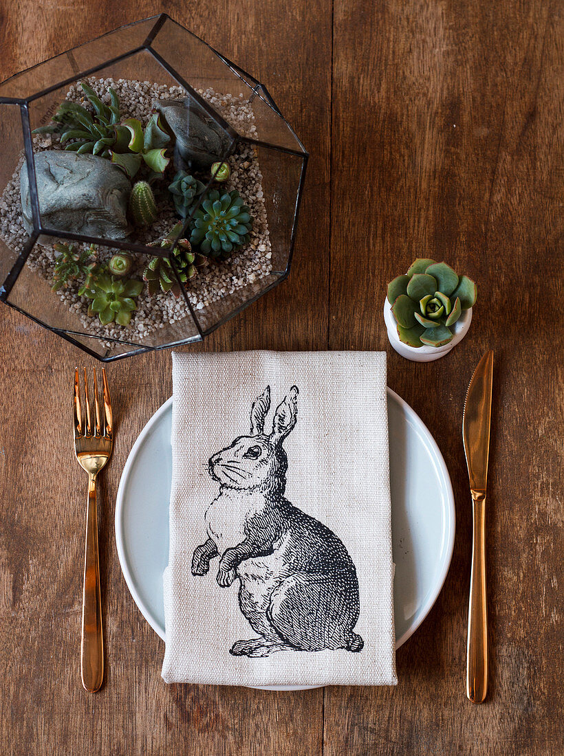 Easter place setting with linen napkin and arrangement of succulents on wooden table