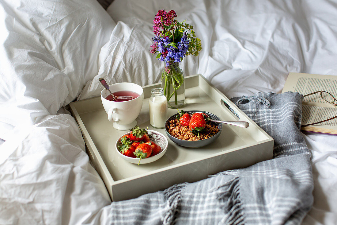 Breakfast in bed with fruit tea, granola, milk and strawberries