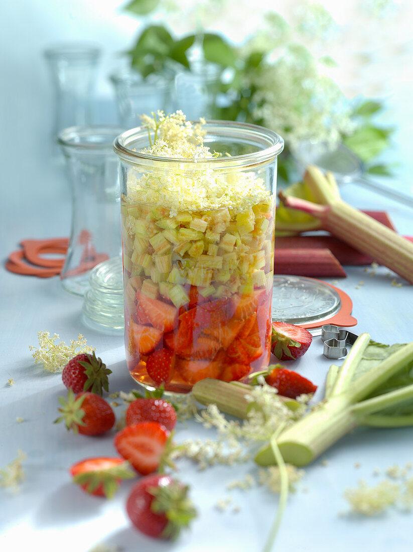 Strawberry vinegar with rhubarb and elderflowers in a preserving jar