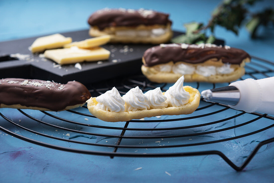 Chocolate eclairs being filled with whipped soya cream