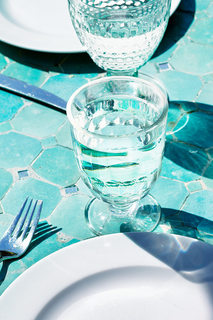 Glasses of water on plates on a tiled floor
