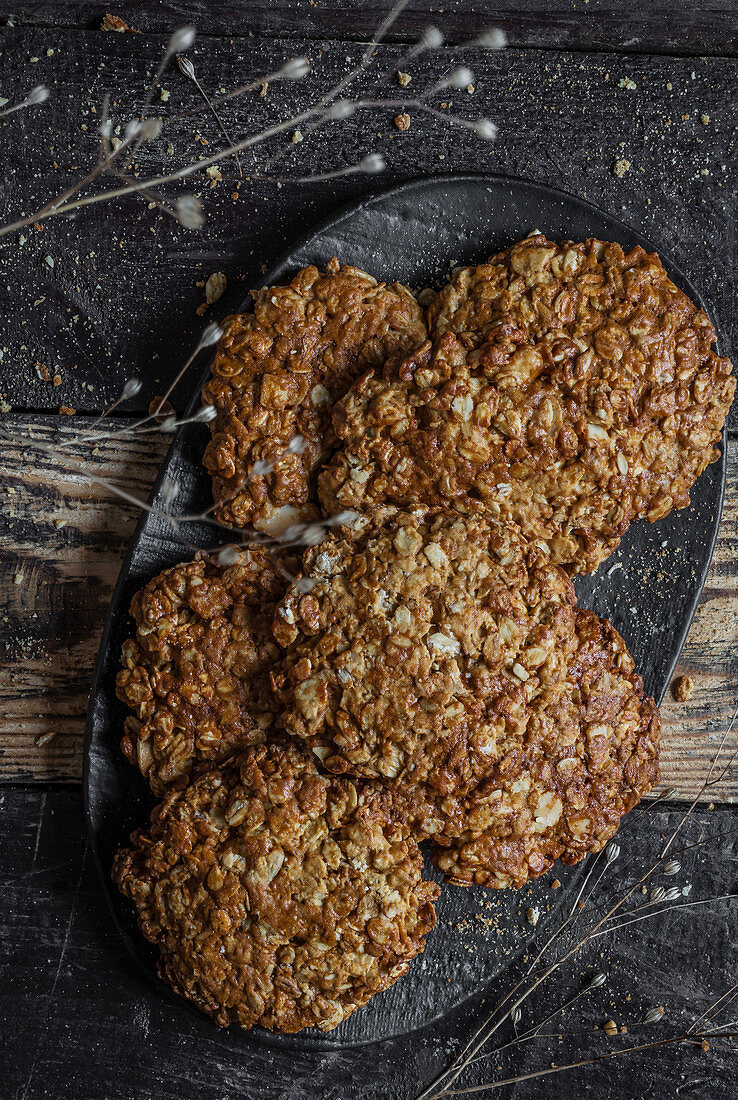 Oatmeal cookies on black plate and wooden background