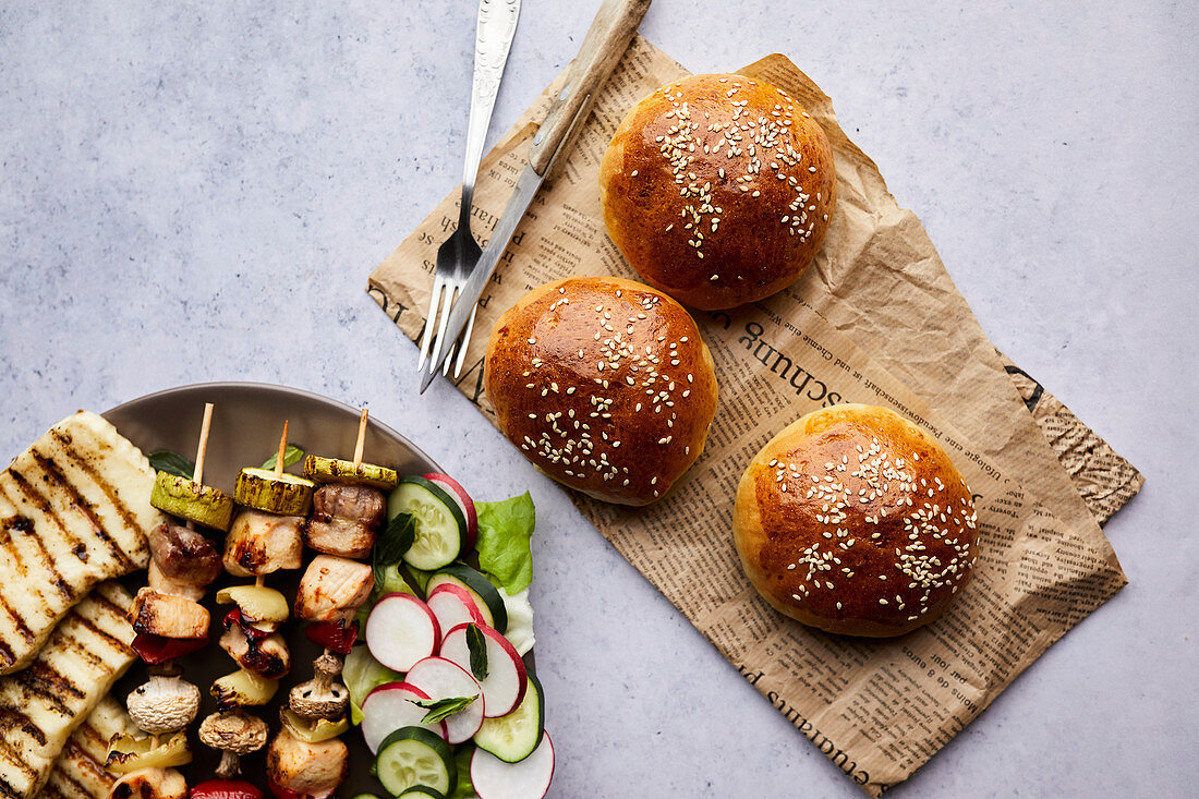 Homemade bread buns served with chicken skewers, grilled halloumi cheese and fresh salad