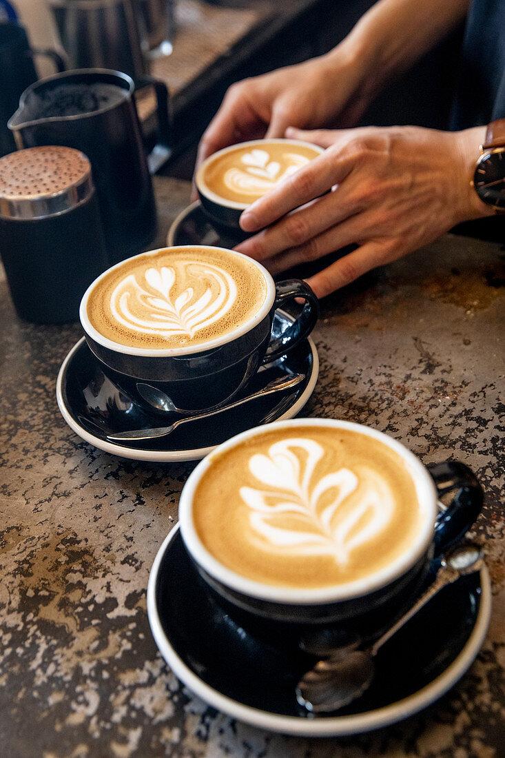 Cappuccinos with milk foam patterns (latte art)
