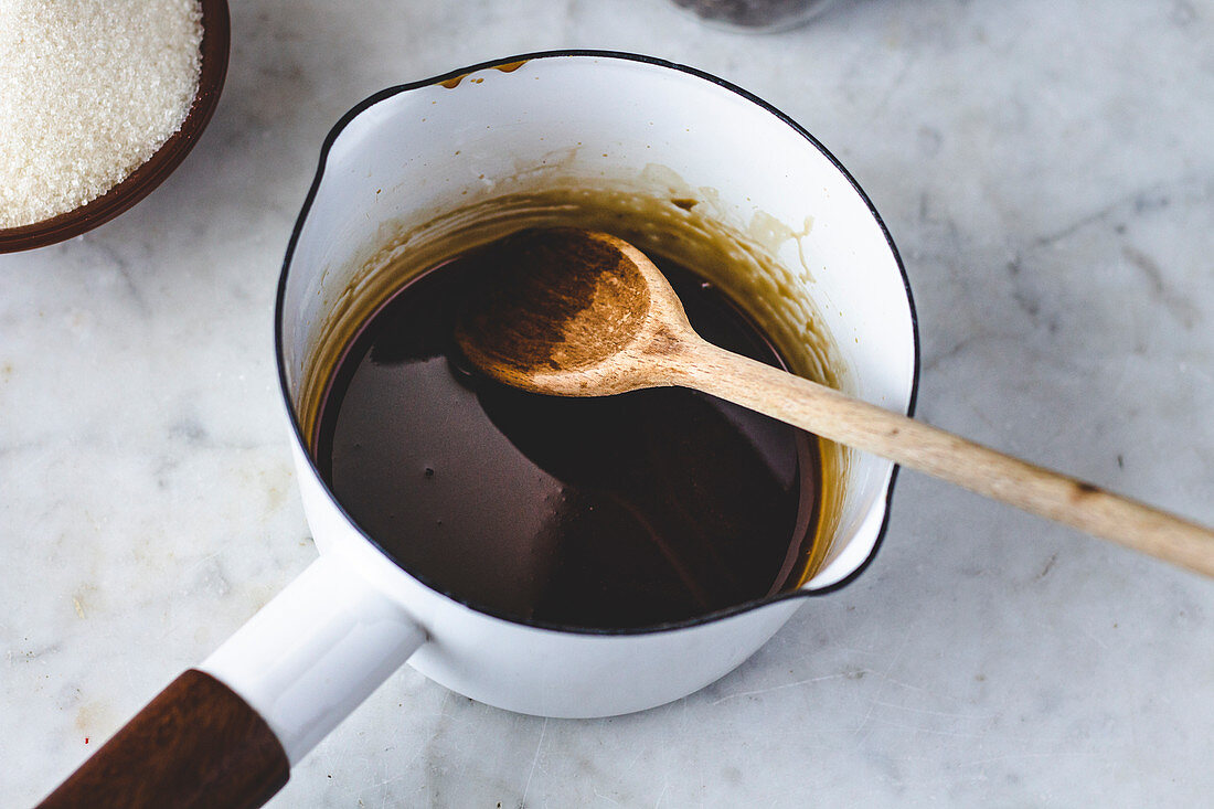 Coffee syrup for Dalgona Coffee being stirred in an enamel saucepan