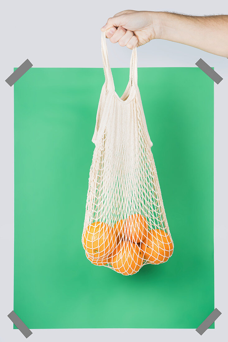 Hand carrying net bag with ripe oranges against green rectangle during zero waste shopping
