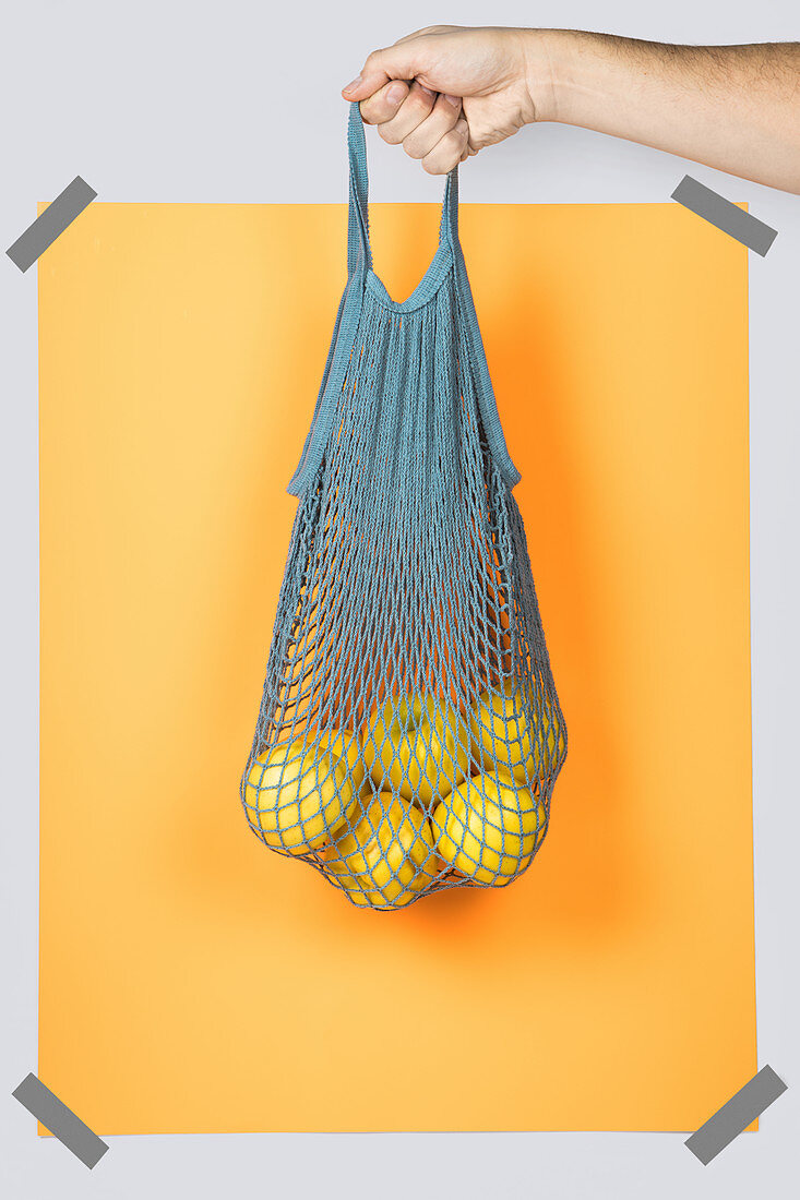 Hand carrying net bag with ripe apples against orange rectangle during zero waste shopping