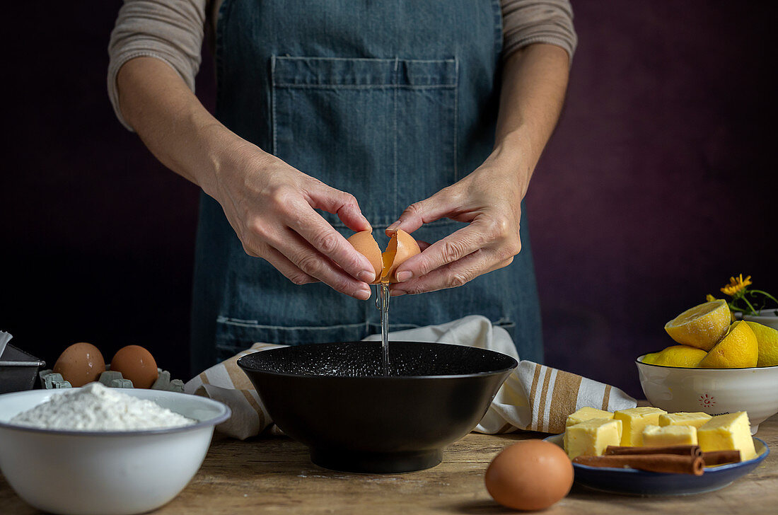 Breaking fresh chicken egg into bowl while cooking pastry in a wooden table with fresh ingredients
