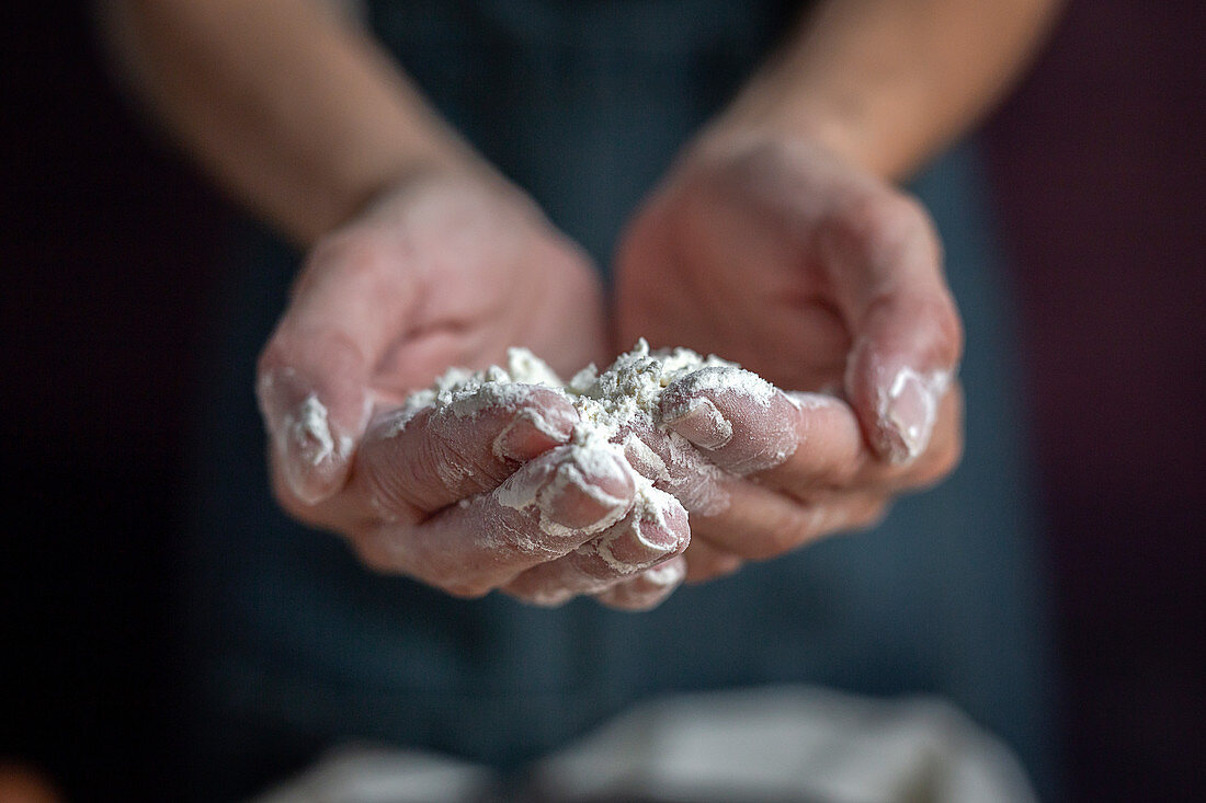 Hands full of flour near black bowl while preparing pastry at home
