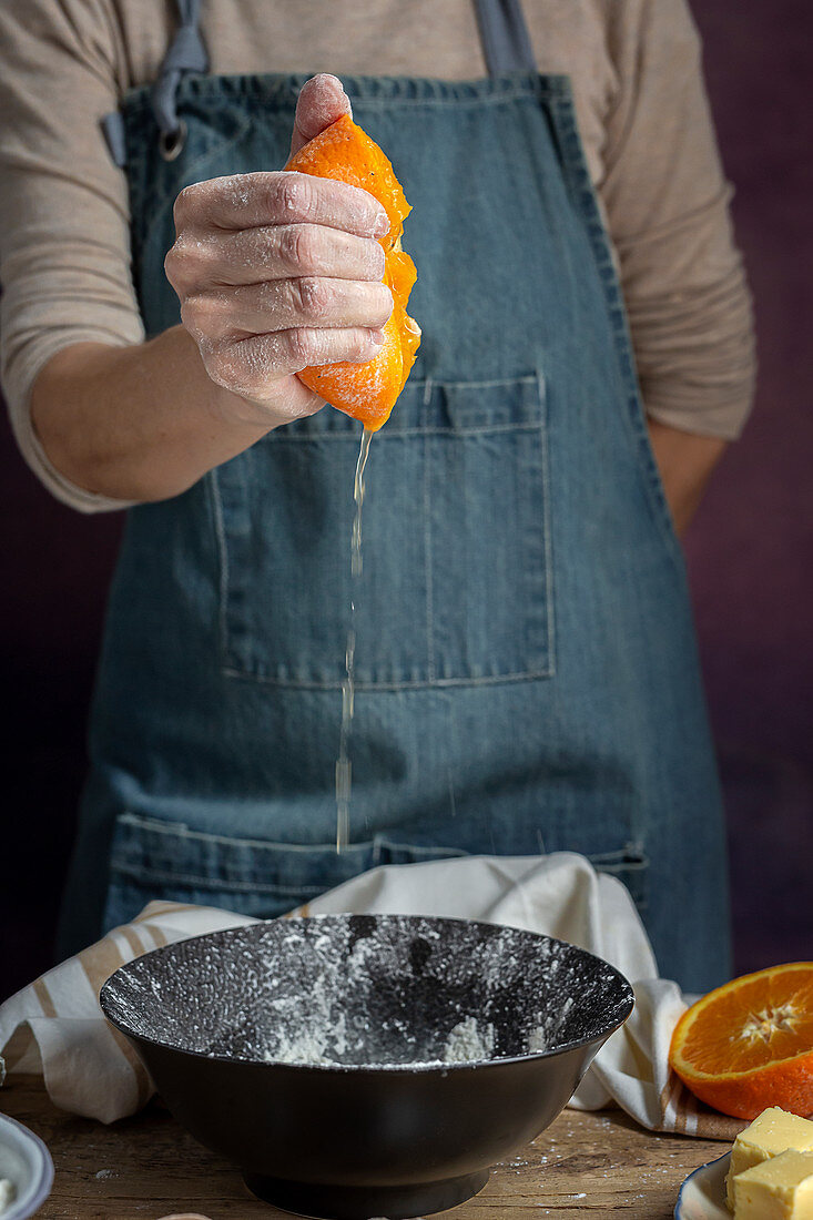 Squeezing fresh juicy cut orange over bowl while preparing dough at table