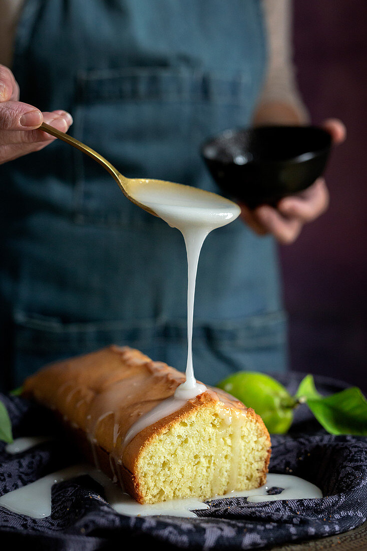 Pouring white sweet glaze on a homemade lemon cake