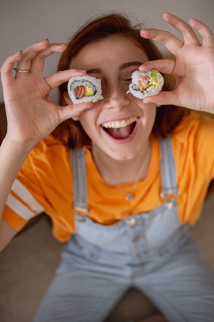 Young female keeping tasty sushi near eyes while having lunch at home