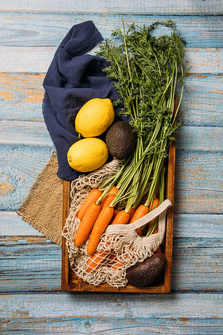Harvested ripe carrots with green foliage, lemon and fresh avocado placed on cutting board