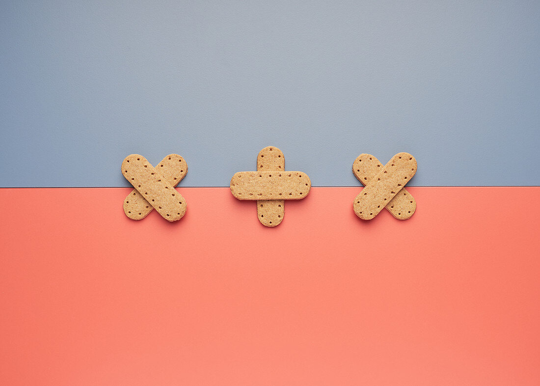 Delicious crispy cookies arranged in shape of crossed patch on line between gray and coral backgrounds