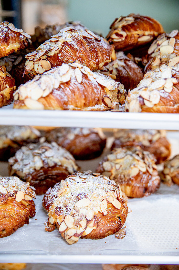 Sweet puff pastries with flaked almonds in a bakery