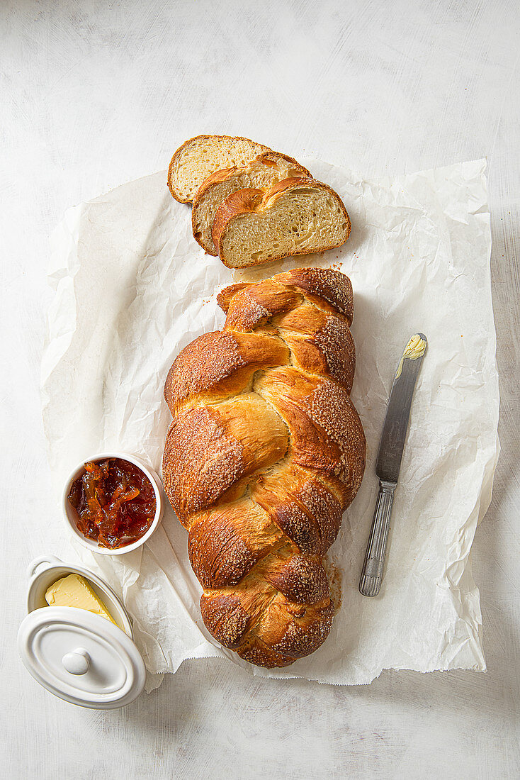 Sweet bread sliced with a pot of marmalade and butter