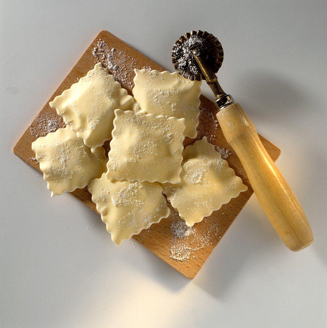 Homemade Ravioli on a Board; Pasta Knife