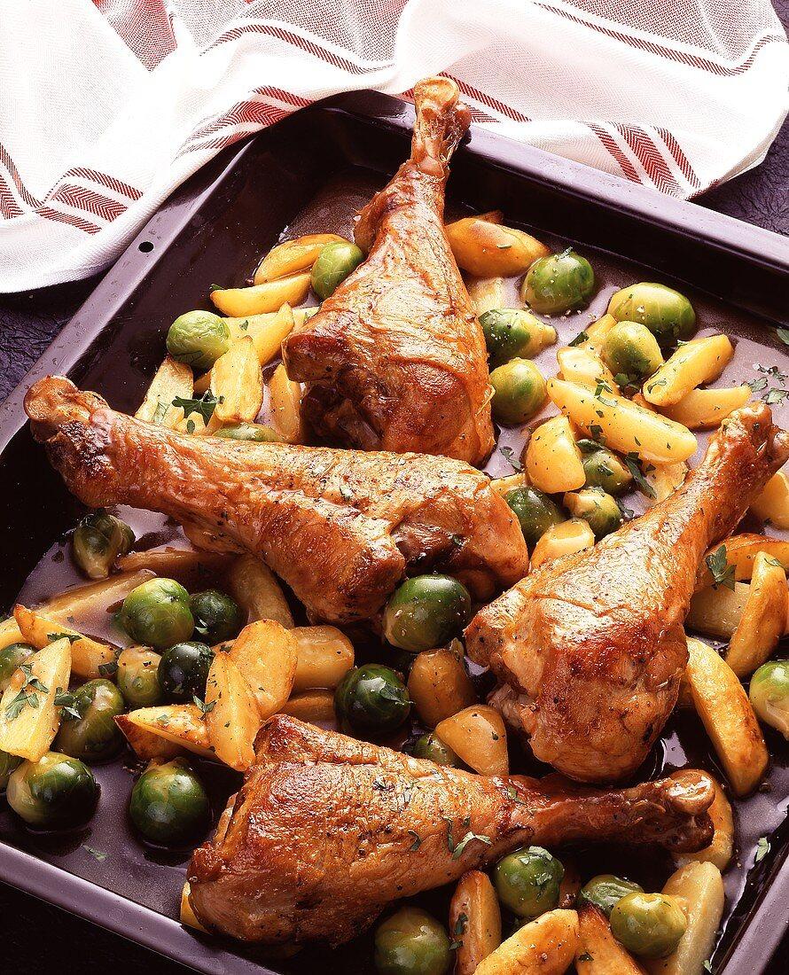 Turkey legs on Brussels sprouts & potatoes on baking sheet