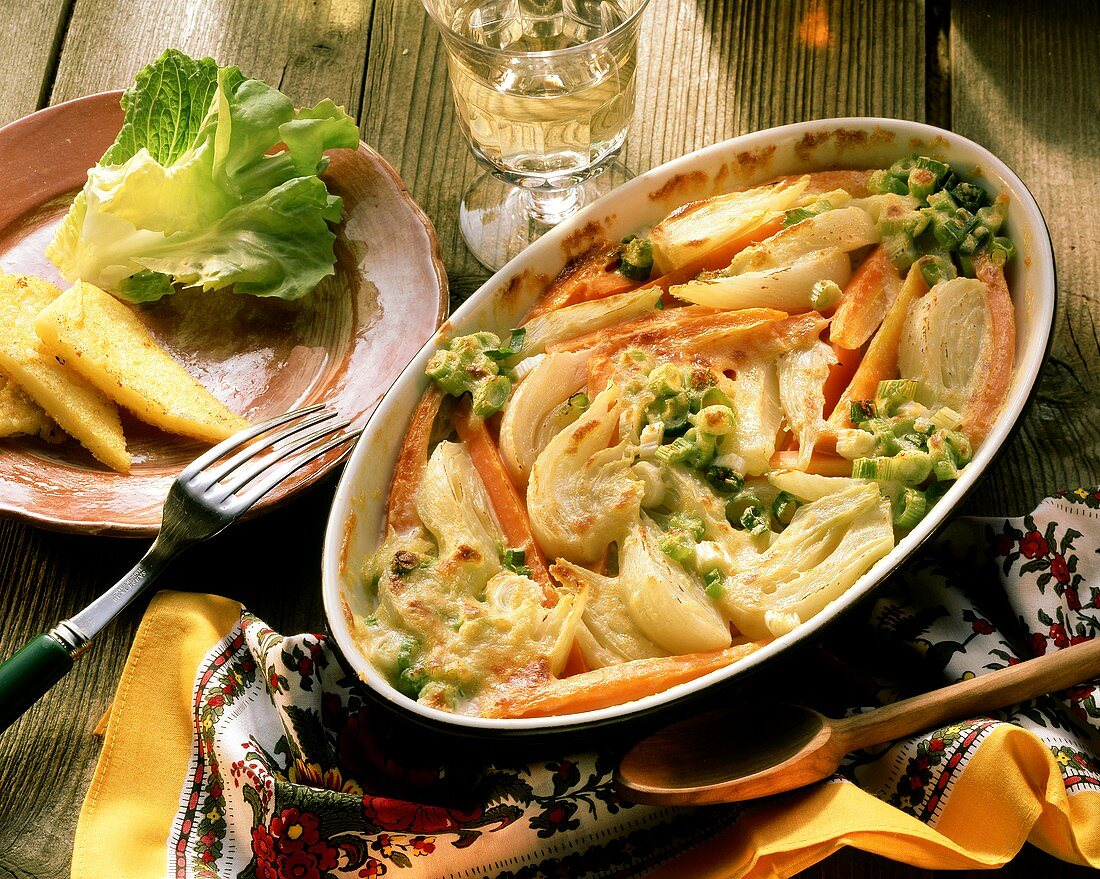 Fennel and carrot gratin with sliced leeks in gratin dish
