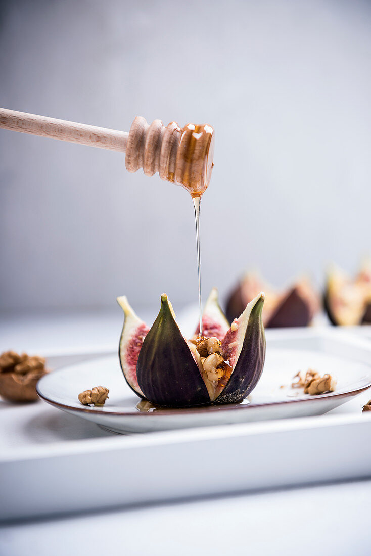 An oven-baked fig filled with walnuts and almond cheese being drizzled with syrup (vegan)