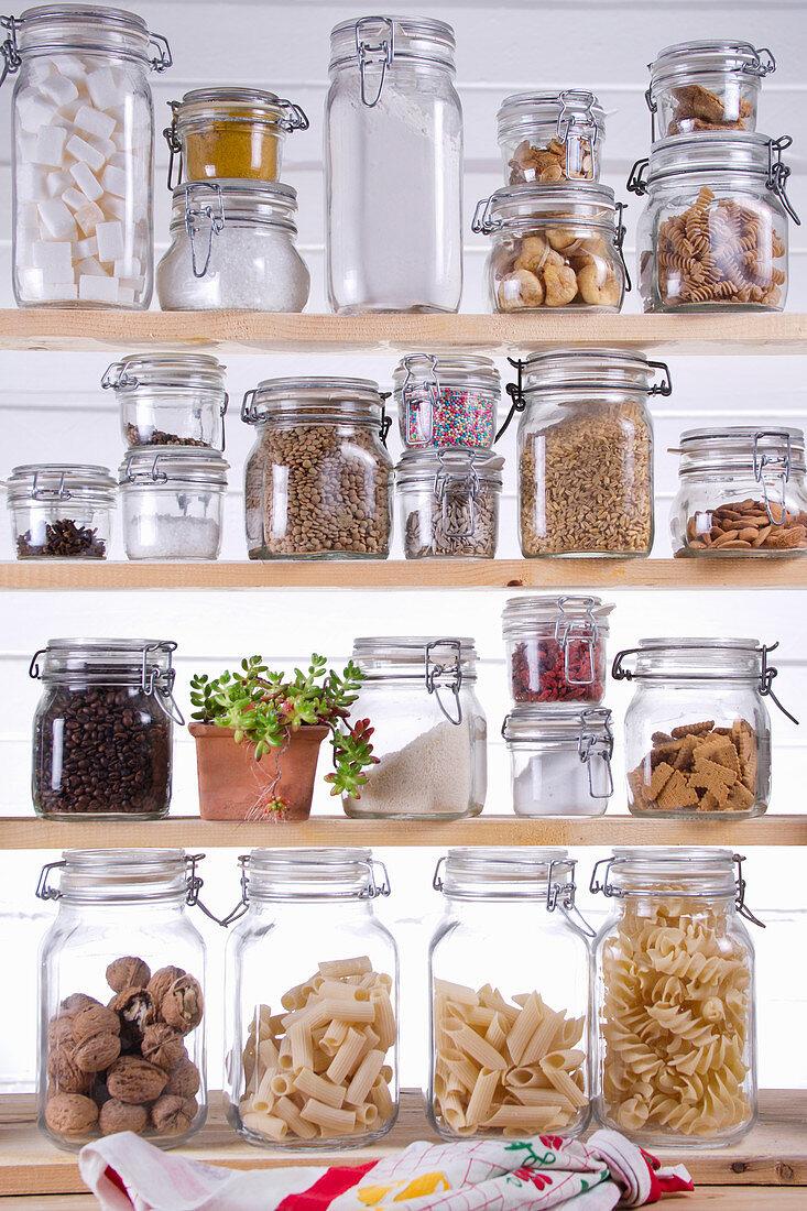 Food in storage jars on a wooden shelf