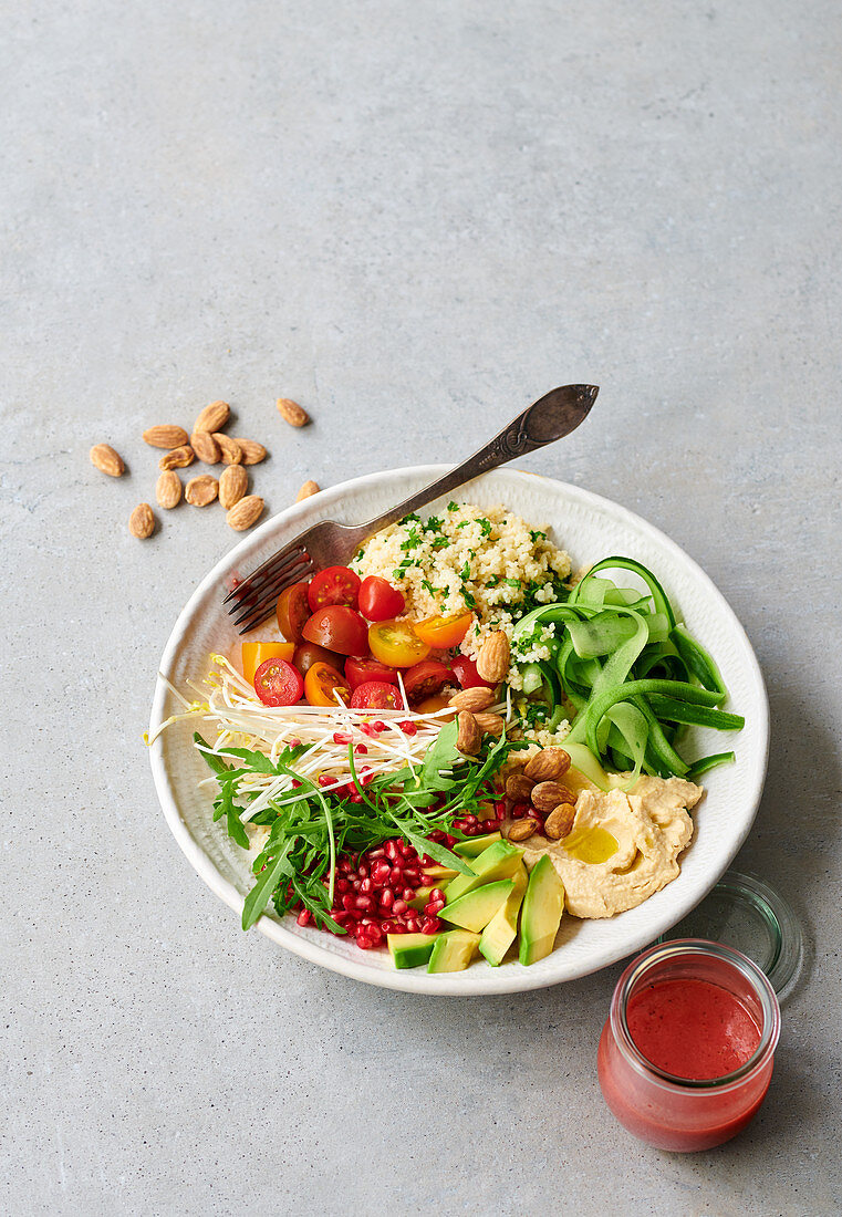 A salad bowl with couscous, vegetables and a fruity dressing