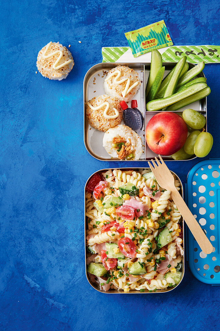 Lunchbox with pasta salad, sushi rice balls, fresh fruits and vegetable