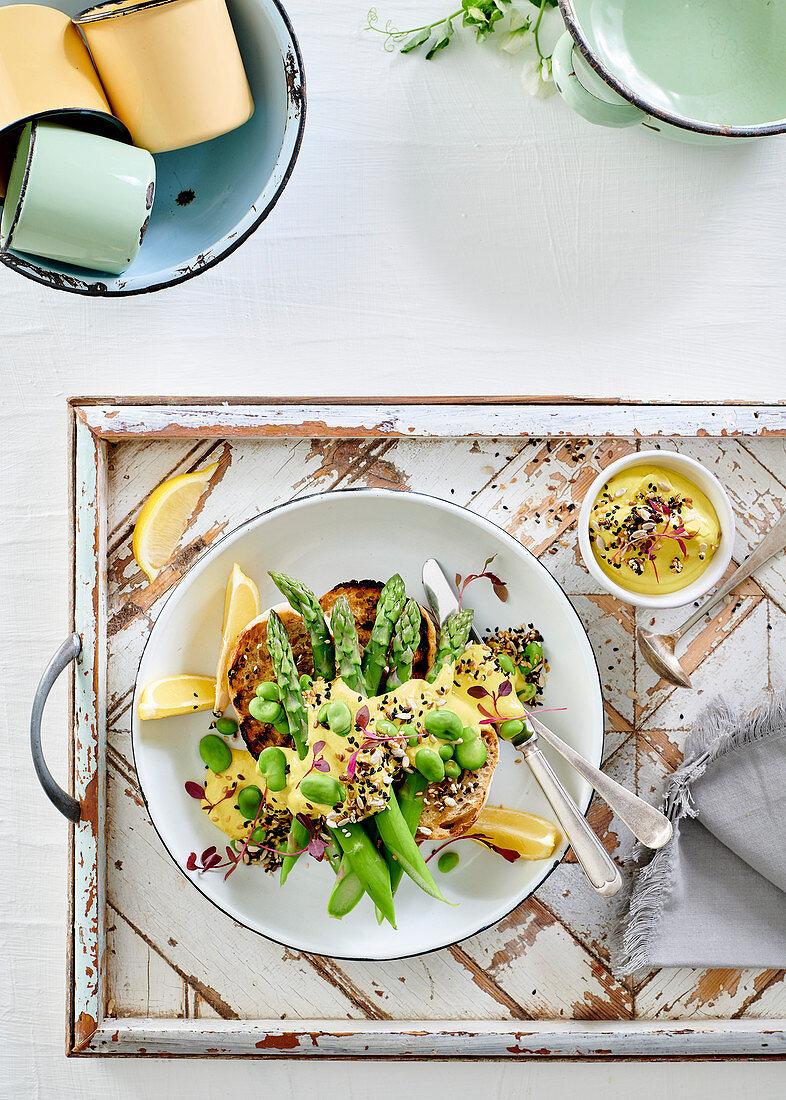 Broad beans, edamame and asparagus on sourdough with vegan hollandaise