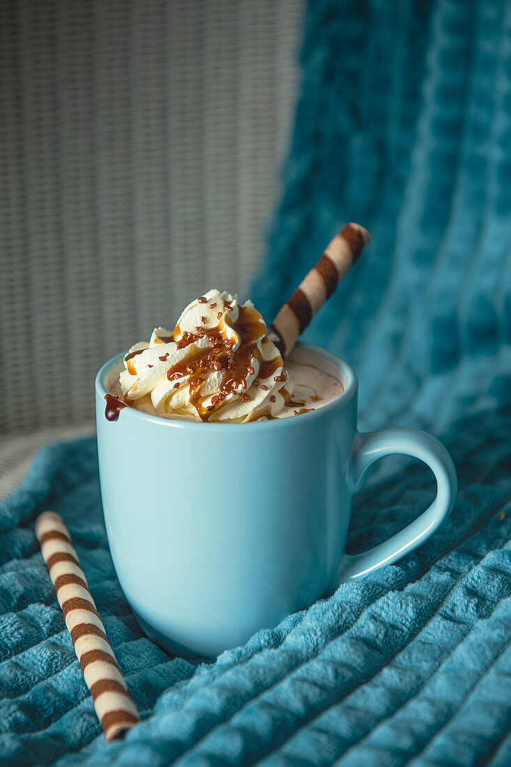 Hot chocolate with whipped cream, toffee sauce and biscuits