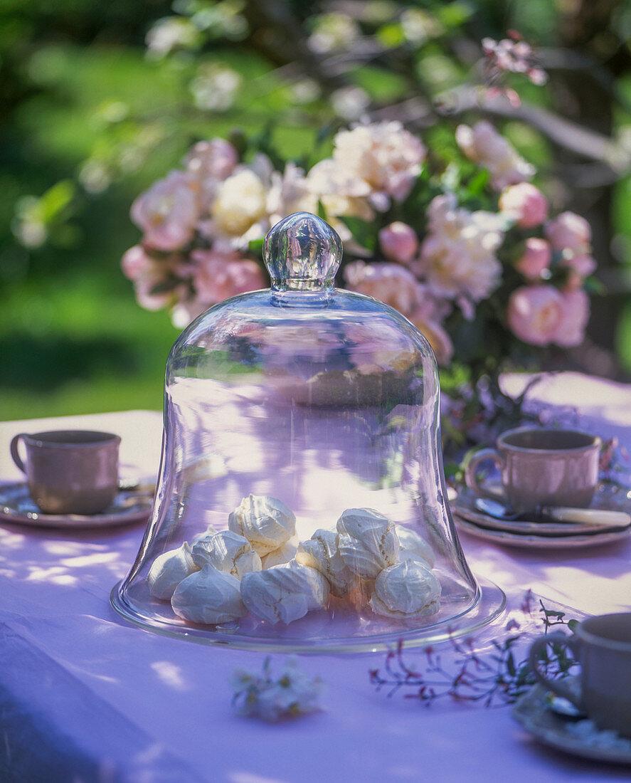 Meringue bites under a glass cloche on a garden table
