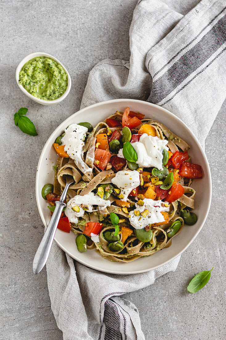 Tagliatelle with courgette, broad beans, tomatoes and pesto