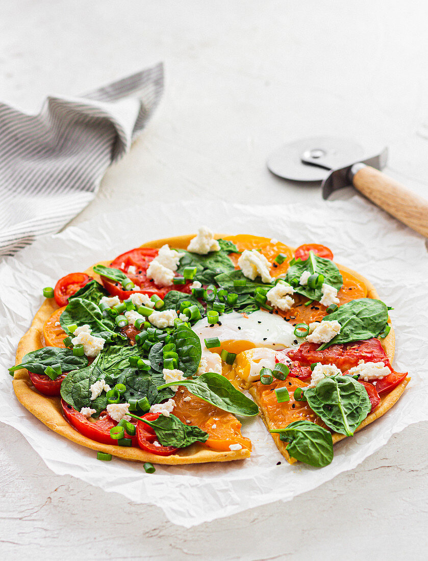 Socca pizza with spinach, tomatoes and egg