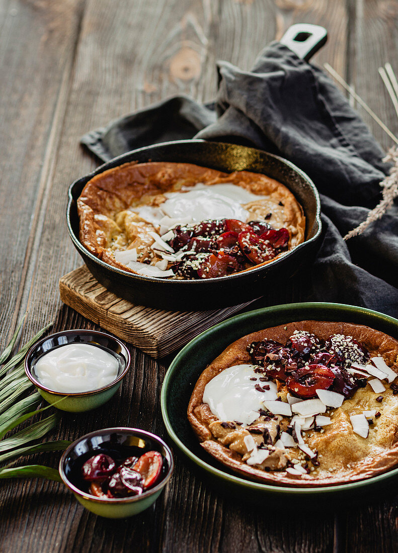 Dutch Baby with coconut chips, coconut yoghurt and plums