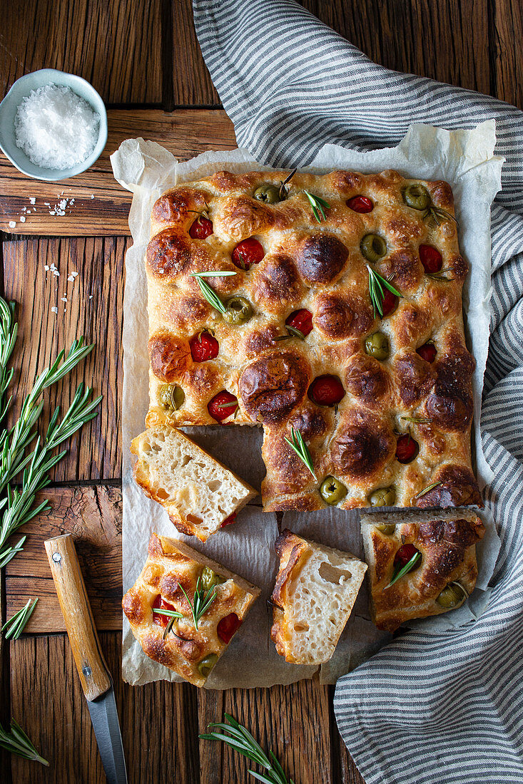 Overhead potato focaccia with fresh rosemary placed near bowl with salt and striped napkin on wooden table