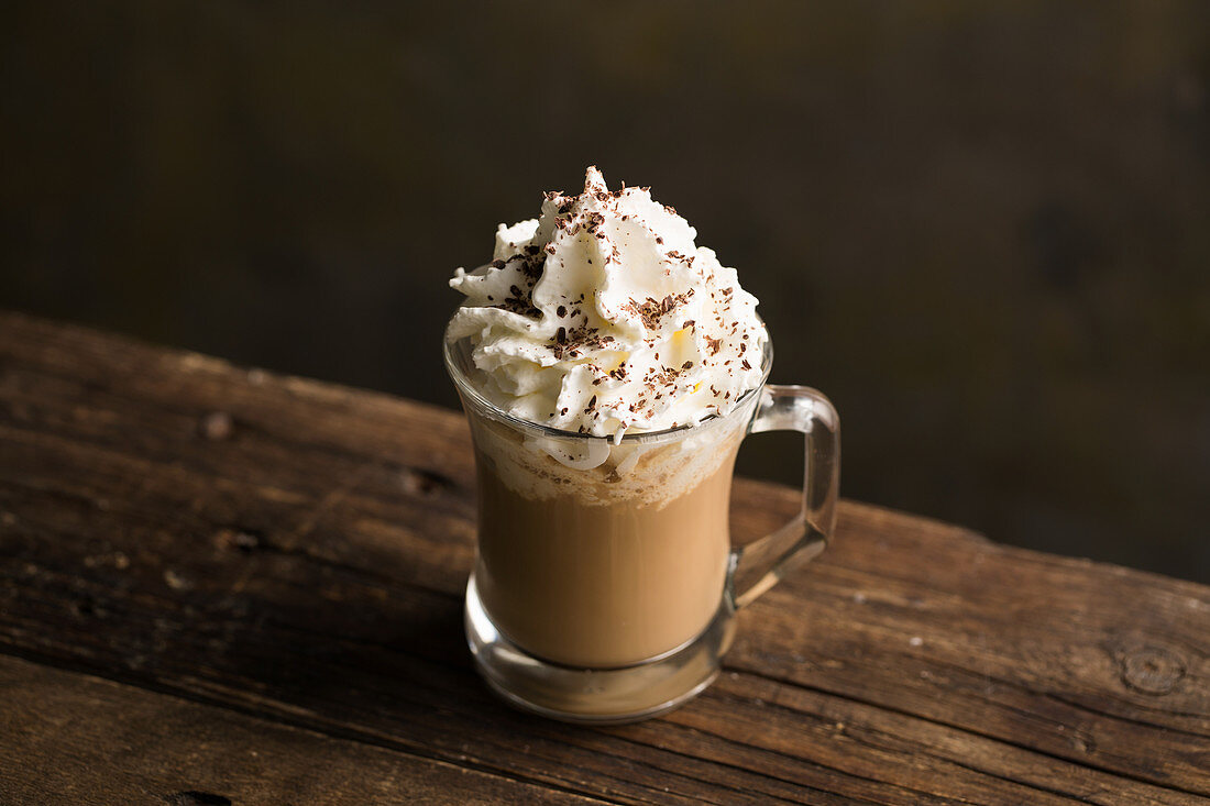 From above delicious fragrant brown beverage with white cream and chocolate sprinkles on top in glass cup on wooden table