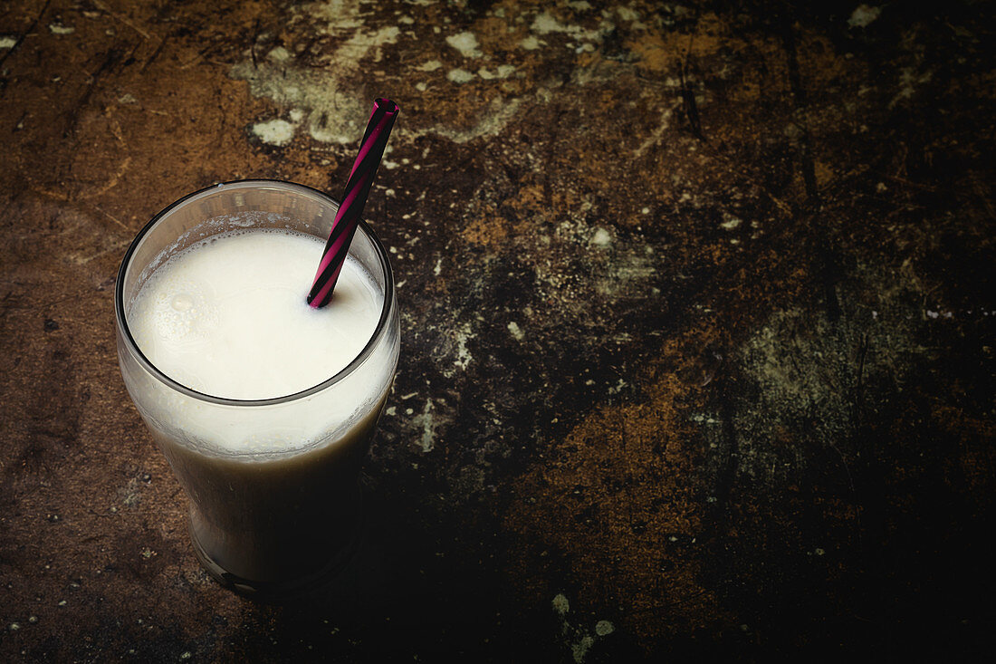 Tall glass of white milk with bright striped straw on table over black background
