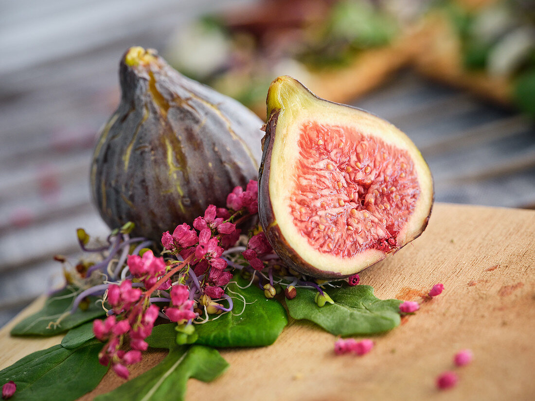 Ripe whole half and sliced figs among flavored green leaves of herbs and colorful flowers