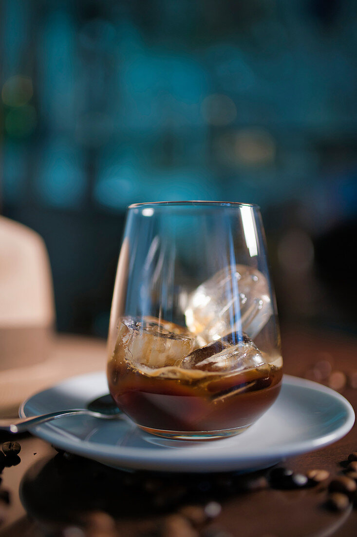 Delicious aromatic brown beverage in glass on round saucer standing among roasted coffee beans beside hat with brim on wooden glossy table