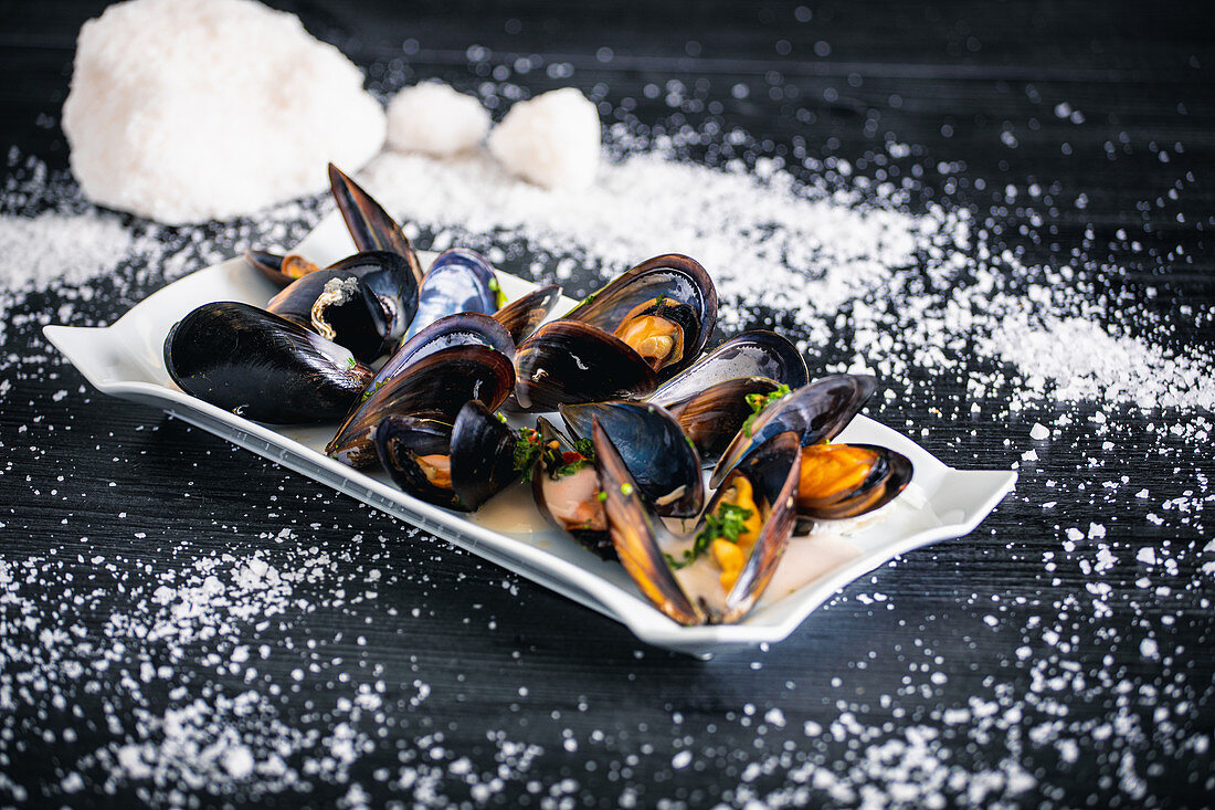 Steamed mussels with Thai sauce in white plate