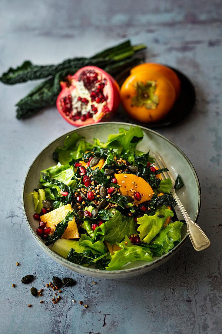 Autumn salad with cabbage, batavia lettuce, persimmon and pomegranate (vegan)