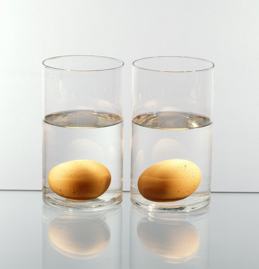 Two Glasses of Water; Each with a Brown Egg