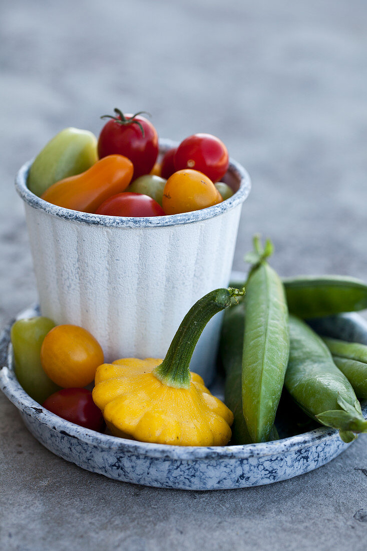 Various vegetables - colourful cherry tomatoes, snap peas, and yellow and green zucchini