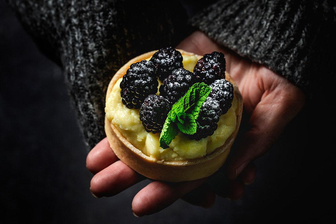 Hand hält Tartelett mit Vanillecreme und Brombeeren