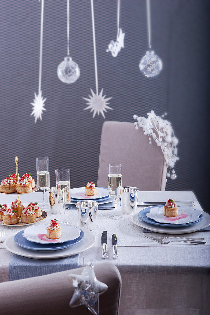 A laid Christmas table with champagne glasses and puff pastry tarts