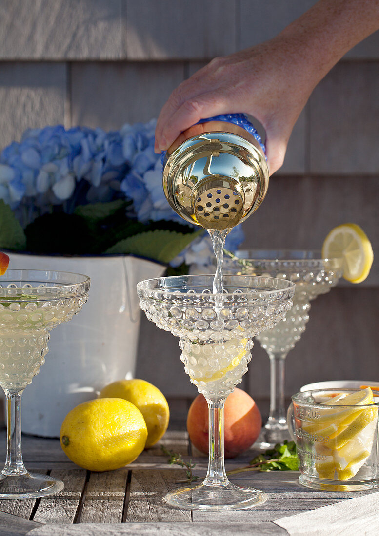 Vodka lemonade being poured from a shaker into a glass on an outdoor table with flowers, lemons, peaches, thyme and mint