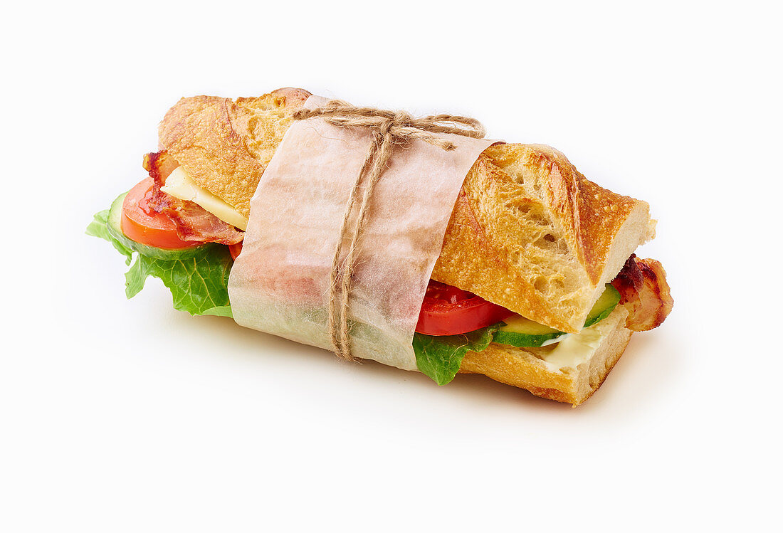 Fresh big baguette sandwich with bacon, chedder cheese, mustard, lettuce and vegetables