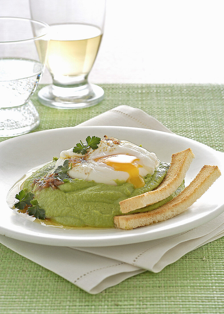 Poached egg on pea puree with toasted bread sticks