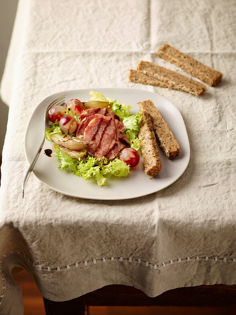 Cotechino on a salad with caramelised grapes